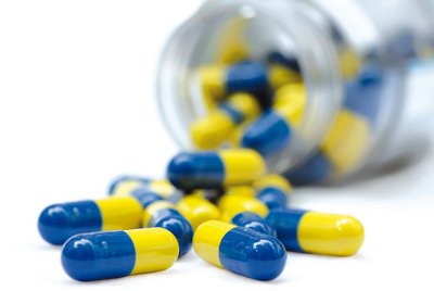 Yellow and blue pills spilling out of a white bottle