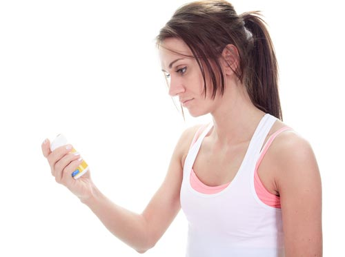 woman in excercise clothes reading a medicine bottle