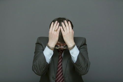 Stressed businessman with hands over his head
