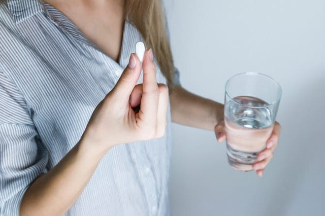 Woman about to take a white pill with a glass of water
