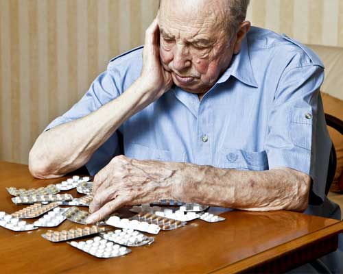 elderly-man-addicted-to-pills-sadly-looks-at-pills-on-table